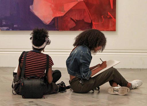 Young people drawing infront of Art work